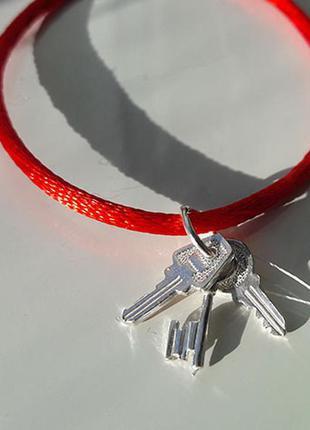 Браслет шелковая нить красного цвета c серебряной застежкой.