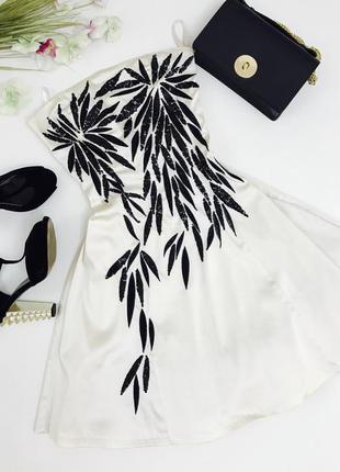 Вечернее платье с красивой пышной юбкой и вышитыми паетками в виде контрастных черных цветов.