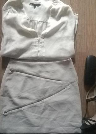 Короткая юбка отдекорирована симметрично молниями