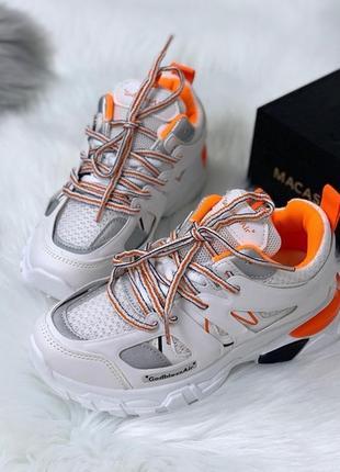Стильные белые кроссовки с оранжевыми вставками.