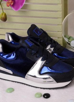 Черные с синим кроссовки с серебристыми вставками.