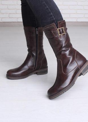 Кожаные коричневые сапоги на низком каблуке с пряжкой.