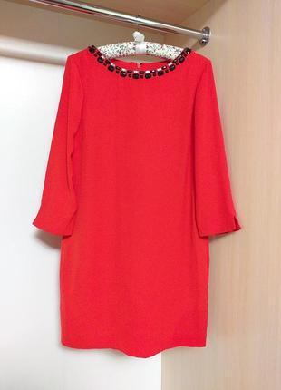 Яркле красное платье прямого кроя с украшением на шее и красивой спиной