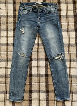 Синие джинсы с потертыми коленями