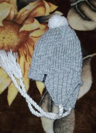 Серая вязаная шапка с ушками косичками
