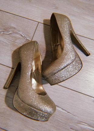 Блестящие золотые туфли atmosphere
