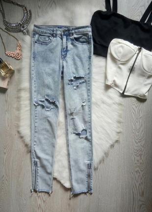 Светлые голубые джинсы варенки с дырками молниями снизу необработанным краем