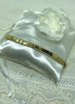 Новая беленькая атласная свадебная подушечка с цветком и золотой лентой