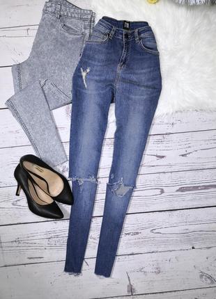 Синие высокие джинсы с фабричными рваностями и необроботанным низом