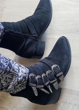 Замшевые чёрные ботинки козаки с множеством металлических пряжек.