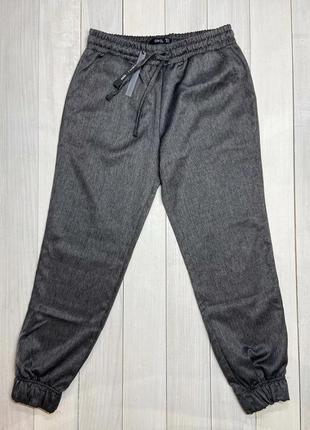 Темно-сірі брюки.