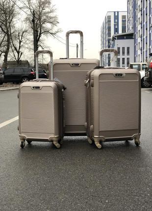 Комплект чемоданов из противоударного пластика цвета шампань с фурнитурой в цвет