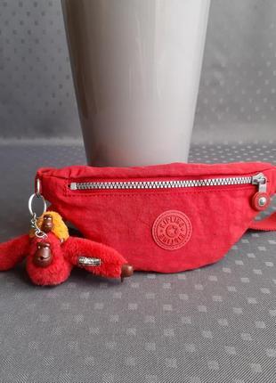 Красная напоясная сумка фирмы kipling