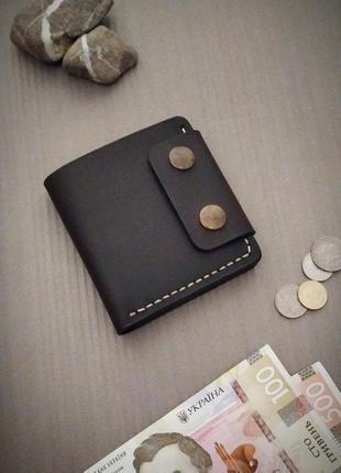 Мужской кошелек из натуральной кожи темно-коричневого цвета.