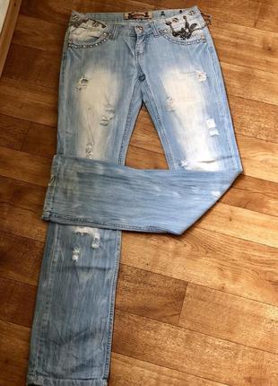 Стильные голубые рванные джинсы