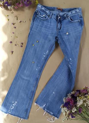 Клешные джинсы с фабричными потертостями, обрезанными штанинами