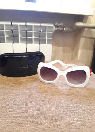 Солнцезащитные очки в белой оправе.