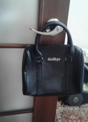 Маленькая черная сумка с короткими ручками.