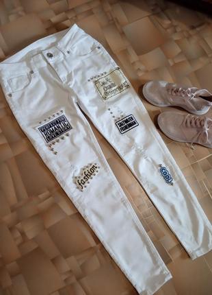 Стильные белые брюки с рваностями и нашивками.