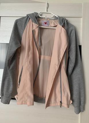Женская ветровка с карманами на молнии и капюшоном.