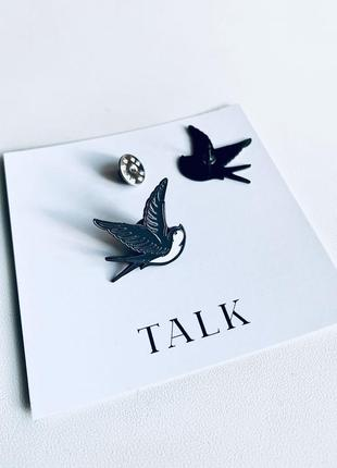Черный пин-значок в форме брендовой ласточки talk