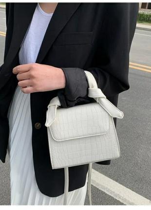 Біла сумочка з тисненням