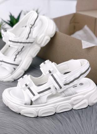 Білі босоножки із рефлексивними вставками