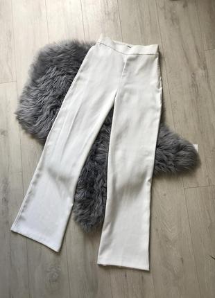 Белые свободные брюки на высокой посадке клёш от бедра