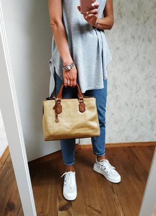 Бежевая сумка с ручками и длинным ремнем.