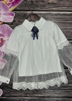 Блуза украшена брошкой и кружевом