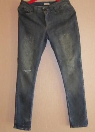 Темно-синие джинсы с потертостями и дыркой