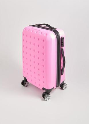 Розовый чемодан на колесах