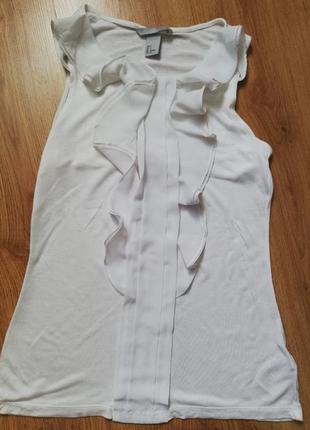 Белая блуза из вискозы без рукавов с воланами.