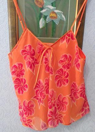 Яркая маечка мандаринового цвета с цветочным принтом
