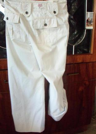 Брендовые спортивные штаны цвета топленого молока.со множеством карманов и хлястиков.