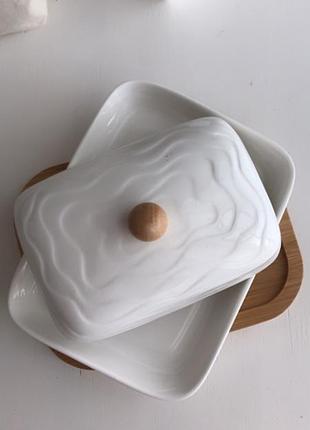 Біла порцелянова масляне а на бамбуковій підставці белая маслянка на подставке