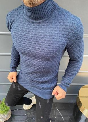 Сиреневый свитер под горло с рельефным узором.