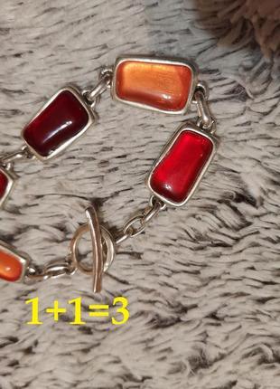Красивый браслет с красными камнями под серебро.