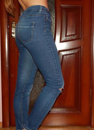 Стильные синие джинсы с дыркой на колене