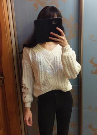 Укороченный рваный свитер с косами и рукавом фонариком молочного цвета