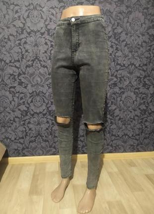 Рваные джинсы серого цвета.