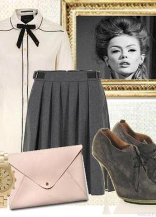 Шерстяная юбка в складку серого цвета, длиной до колен.