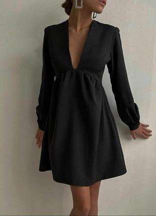 Короткое черное платье с глубоким v-образным вырезом.