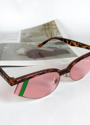 Стильні сонцезахисні окуляри з леопардовою оправою та рожевими лінзами.