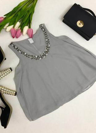 Красивая многослойная блузка с украшением на горловине.