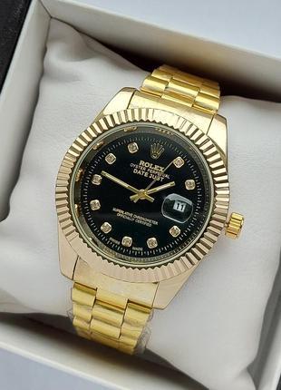 Чоловічий наручний годинник золотого кольору з чорним циферблатом, на браслеті, дата
