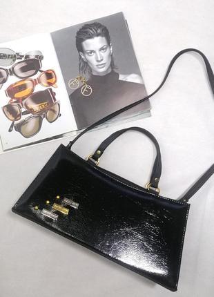 Кожаная черная сумка держит форму лаковая
