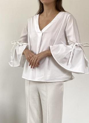 Блуза с бантиками и расклешенным рукавом