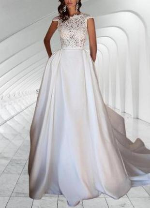 Длинное свадебное платье со шлейфом пышной атласной юбки и открытой спиной