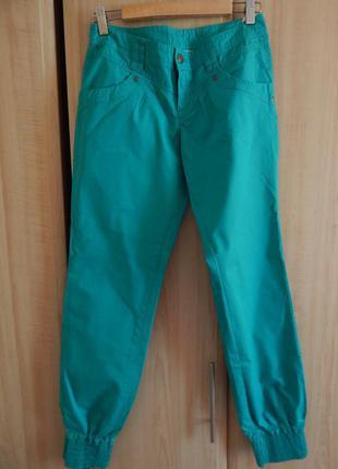 Зеленые брюки, внизу присобраны на резинку